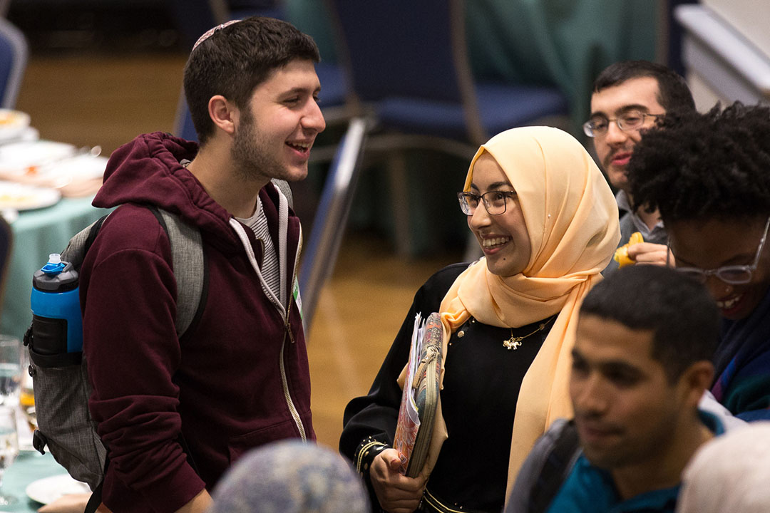 Two students, one wearing a yarmulke and one wearing a scarf, talking and smiling