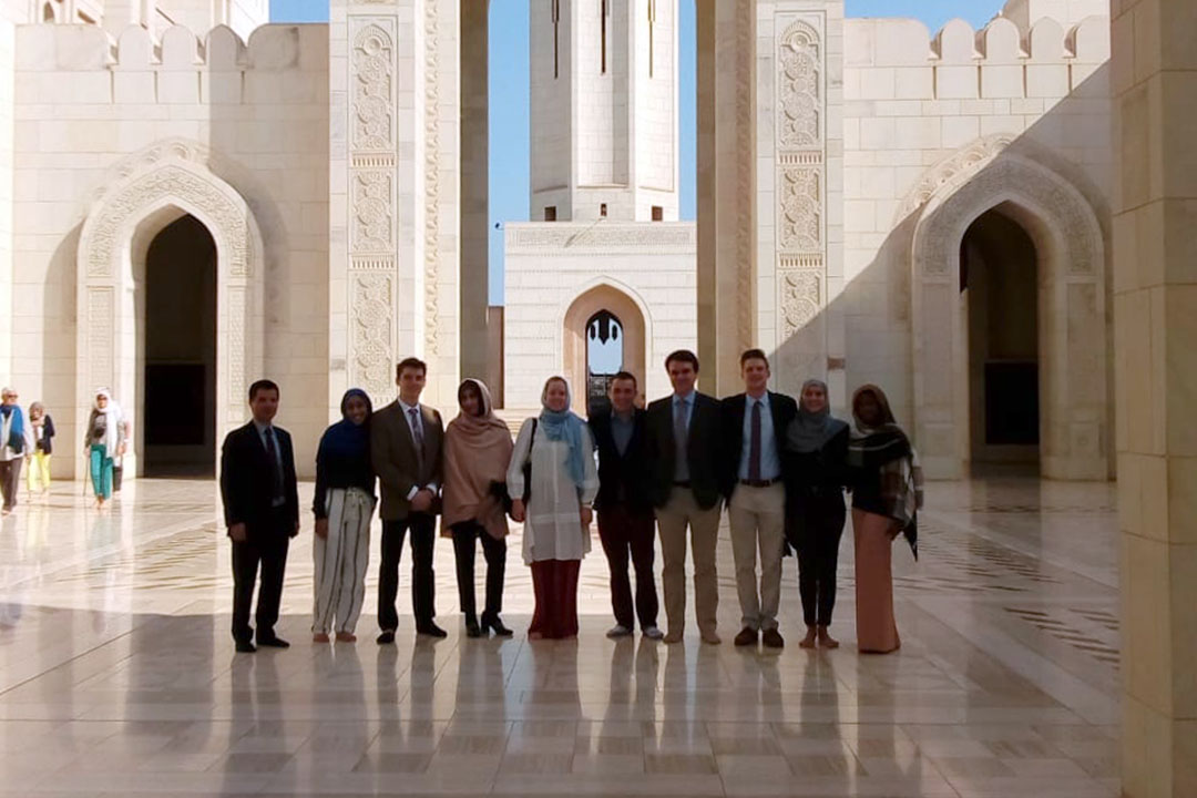 A group of students outside a huge white stone building with tiled floors
